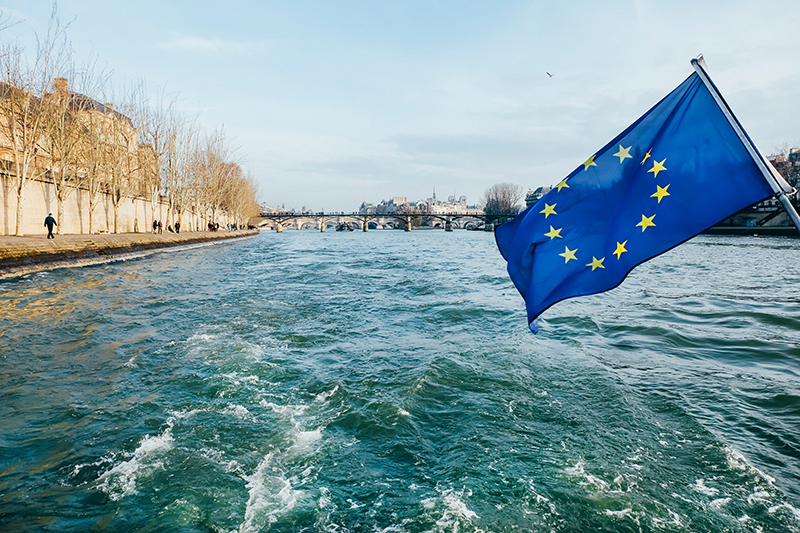 eu flag on a boat in paris on a eu paternity law changes post